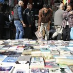 Books are displayed on a pavement in downtown Amman