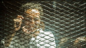 Photo of photojournalist Shawkan behind bars mimicking taking a photo