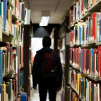 Student with a backpack walking away from library books shelves into darkness.
