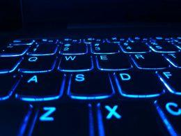 An illuminated computer keyboard. Glowing blue in the dark.